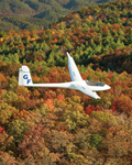 a glider flying over a mountain ridge in Autumn